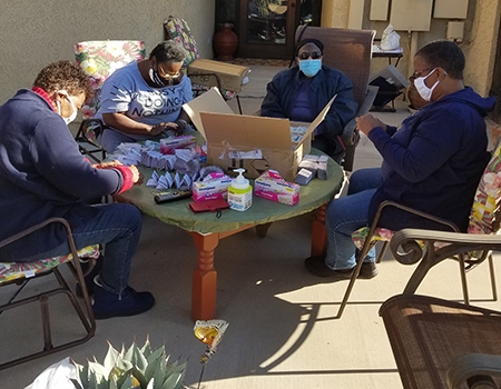 Committee members meet outside to assemble kits for community groups, from left: Wanda Moore, Anita Smith-Etheridge, Marilyn Robinson, Cheryl Alli.