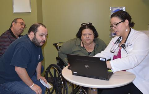 Angelica Lentner, NP, explains data captured by CardioMEMS to patient Deborah Martinez, her husband, Frank, and son, Francisco.
