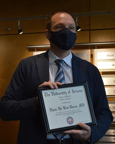 Mathew Hutchinson, MD, virtually presents a diploma to Hyon He K. Garza, MD