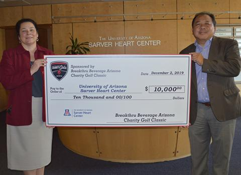 Dr. Nancy K. Sweitzer receives a check from Breakthru Beverage Arizona, with John Fung, development officer